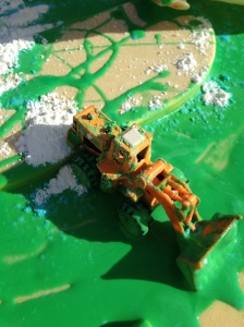 Green gloop recipe outside with sand and a yellow truck.