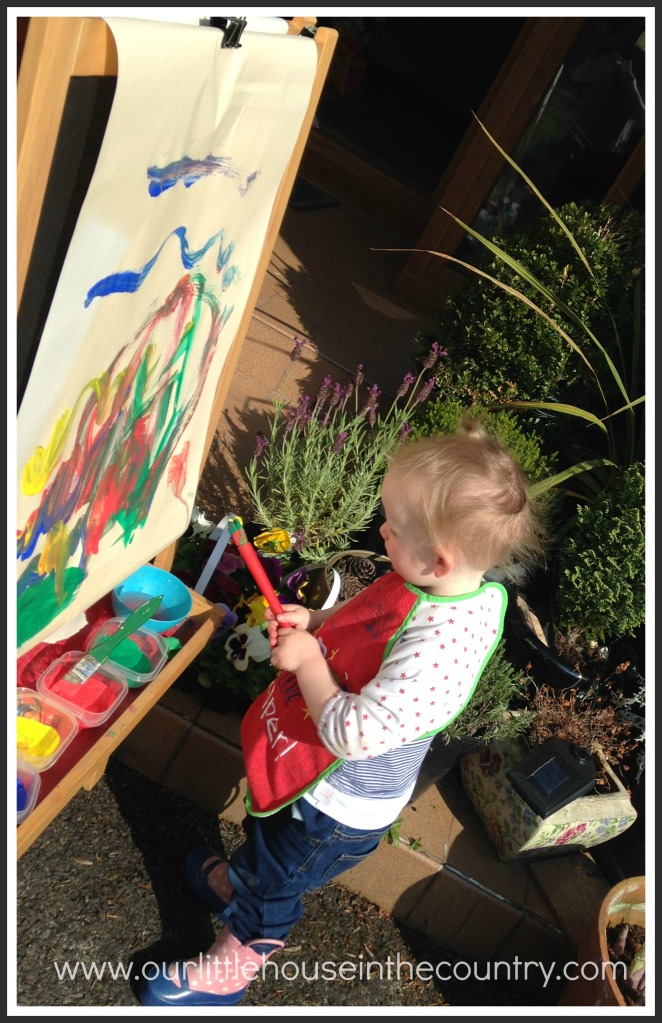 "While D was at preschool the other morning O requested to take her easel outside so that she could ""paint in the sunshine!"""